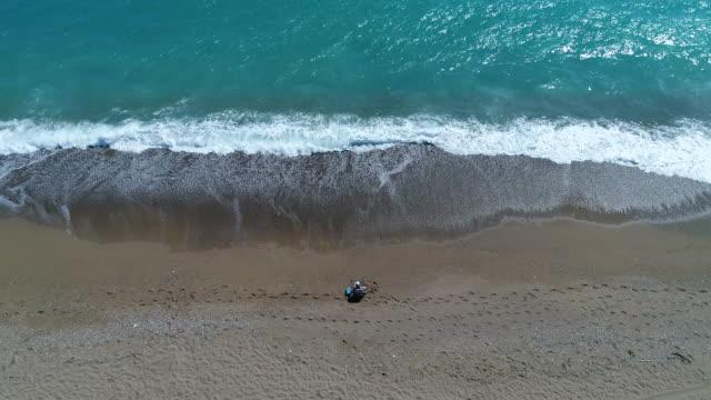 Beach Fisherman by Ocean as Sun rises aerial view. video