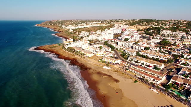 Beach of Praia da Luz at morning, Lagos, Algarve, Portugal aerial view video