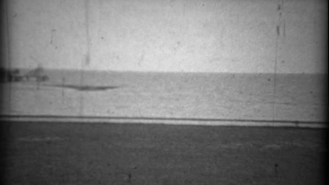 1934: Beach pier sandy view gulf coast sandy bay waters. video