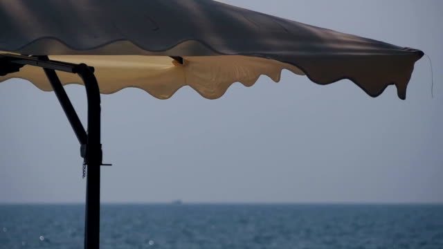 Beach umbrella swinging in the wind close-up video