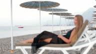 Beach woman enjoying the sea lying on the sun loungeron in the beach video