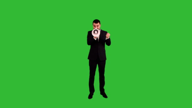 bearded businessman angry and screaming into a megaphone on a green background video