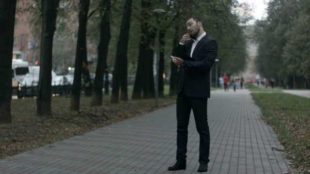 Bearded businessman in park alley talking by phone and writing in diary, working with notes at green park video