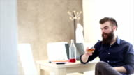 Bearded hipster is drunk at work in the office video