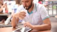 bearded hipster with a tablet in cafe video