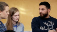 A bearded man in a sweater, gesturing, urges two girls in expediency of his decision video