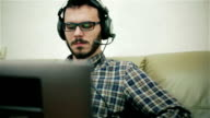 A bearded man in glasses working on a laptop. video