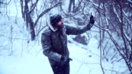 Bearded man make video recording in snowy forest video