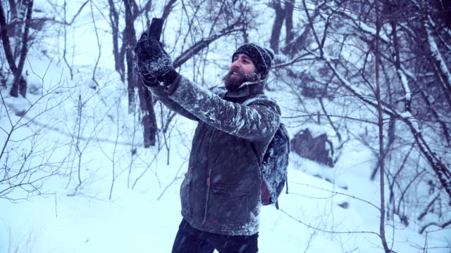 Bearded man making selfie in snowy wood video