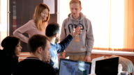 Bearded man sitting at a laptop and gesturing says something to a group of young people video