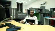 Bearded worker using tablet and having fun at workplace video