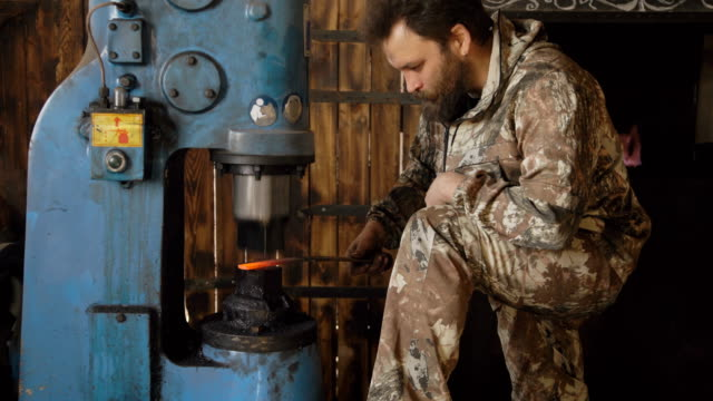 Bearded young man blacksmith using hydraulic press for steel arms manufacture at smithy workshop video