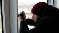 A beardless man with compact camera takes pictures of the winter city from the window from a height video