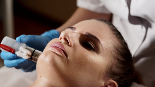 Beautician preparing woman's face for a non-injection mesotherapy treatment. video