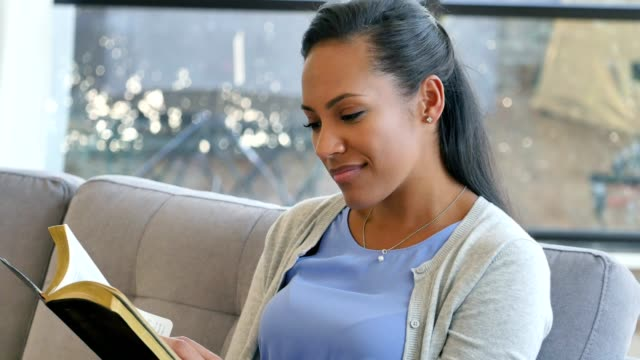 A beautiful African American woman reads the Bible at home video