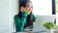 beautiful asian girl talking mobile phone in coffee shop video