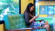 Beautiful asian girl typing mobile phone in coffee shop video