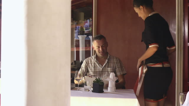 Beautiful Asian waitress serving and talking with client in restaurant video