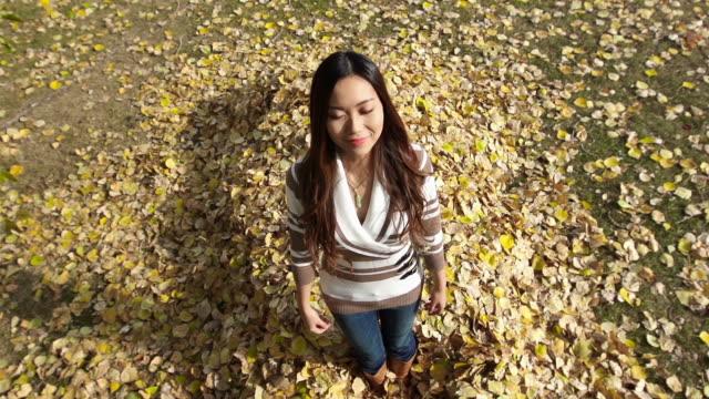 Beautiful Asian woman falls into leaves video