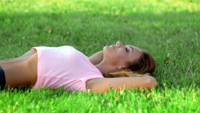 Beautiful athlete resting on the green grass video