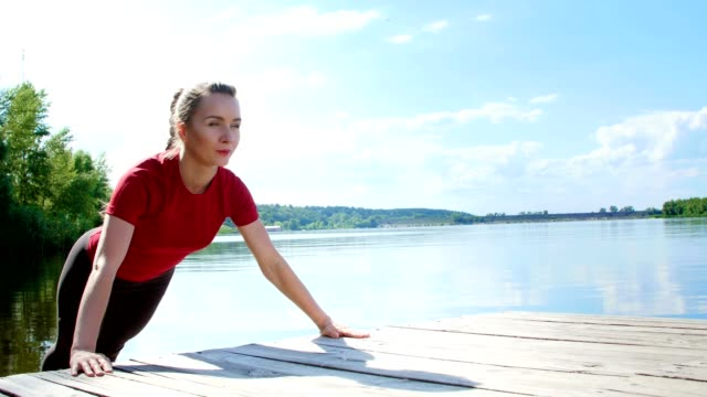 Beautiful, athletic young blond woman stretching, doing push-ups. Lake, river, blue sky and forest in the background, summer sunny day video