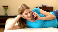 Beautiful attractive young woman in a blue t-shirt lying on sofa and talking on the phone video