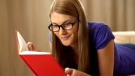 Beautiful attractive young woman in a violet t-shirt and a black glasses lying on a sofa and reading a book video