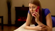 Beautiful attractive young woman in a violet t-shirt talking on the phone video