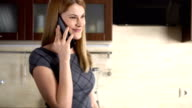Beautiful attractive young woman in grey dress standing in kitchen and talking on the cellphone video