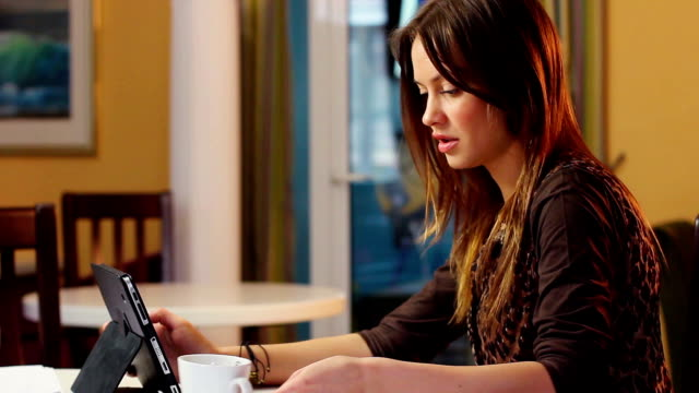 Beautiful attractive young woman reads news in tablet PC office video