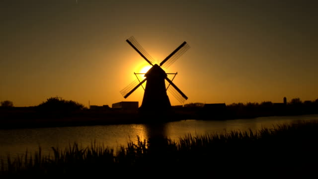 Beautiful authentic old windmill on the river bank at beautiful golden dawn video
