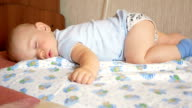 Beautiful baby sleeping in funny pose on a bed. Under the baby diaper, the boy about a year video