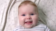 Beautiful baby smiles at camera video
