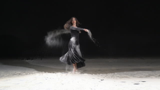 Beautiful ballerina dancing in a pirouette with powder snow at studio. Slow motion video