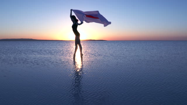 Beautiful ballerina holding a Japan flag on the water. A windy day. Slow motion video
