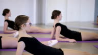 Beautiful ballerinas warms their muscles before training in classroom video