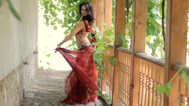 Beautiful barefooted woman with mehendi dancing oriental dance in slow motion video