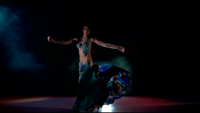 Beautiful belly dance movement of young girl, slow motion, in smoke, black video