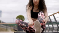 Beautiful black haired, curly fitness model, prepairing for exercise, fixing her sports gear, outdoor video