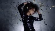 Beautiful black woman among golden confetti, slow motion . video
