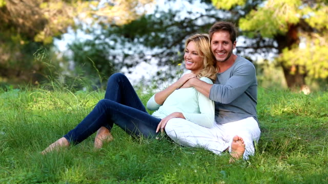 Beautiful blond couple sitting in the green meadow video