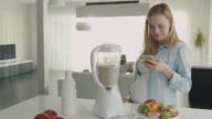Beautiful blond pregnant woman is making a smoothie in blender and using her smartphone. video
