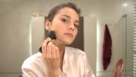 beautiful blonde girl using make up brush video