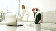 Beautiful blonde sitting in white livingroom video