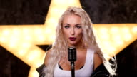 beautiful blonde with curly hair woman Singing it Retro Microphone, shining star in the background, slow motion, close up video