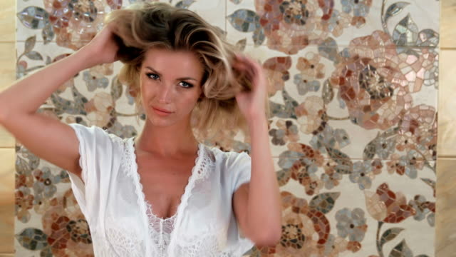 Beautiful blonde woman doing her hair up in front of camera video