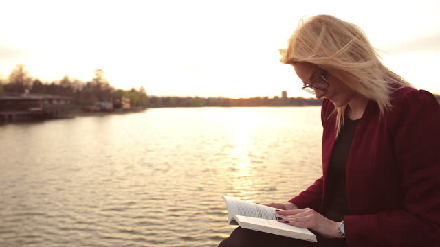 Beautiful blonde woman reading a book on the lake edge video