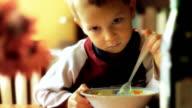 Beautiful boy eating spaghetti. video