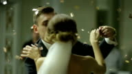 Beautiful brunette bride and handsome groom dancing first dance at the wedding party shrouded by confetti. Very tender moment video