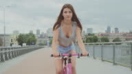 Beautiful brunette girl cycling in big city. Single speed city bike. Recorded with RED EPIC camera. 90 fps video